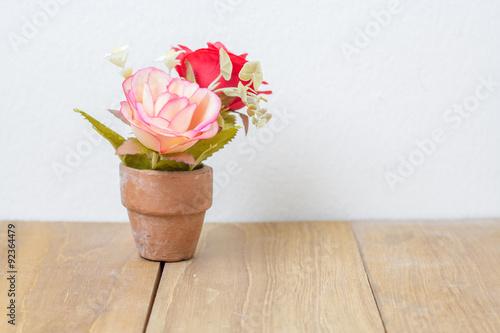 plastic flower in pot on wooden board