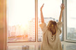 Woman near window raising hands facing the sunrise at morning - 92374605