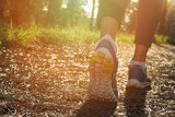 Athlete runner feet running in nature, closeup on shoe. Woman fitness jogging, active lifestyle concept