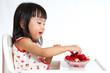 Asian Chinese little girl eating strawberries