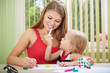 Постер, плакат: Playful baby girl with her mom painting picture by colorful chalks at the table Childhood and togetherness concept