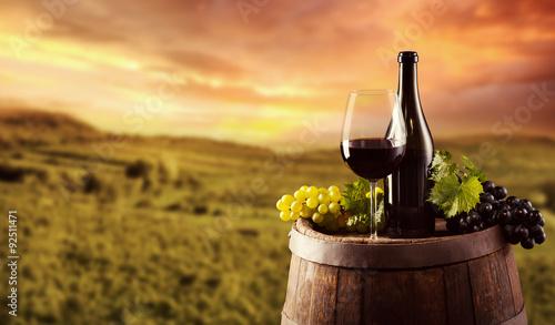 Fototapeta Red wine bottle and glass on wodden keg