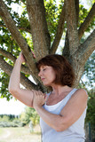 young aging woman in meditation with a tree for revitalization poster