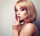Beautiful makeup blonde famale model showing secret sign and loo