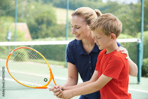 Fotobehang Tennis Female Tennis Coach Giving Lesson To Boy