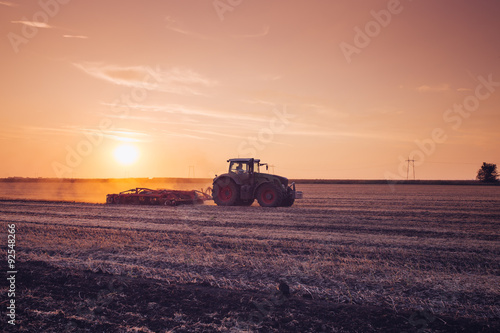 Plakat Tractor on the field by sunset.