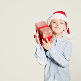 Kid holding Christmas Gift Box. Child Boy and Gift on Background