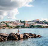 Man with fishing rod against Ibiza townscape poster