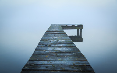 Close up of old, wooden jetty in the autumn fog. © sanderstock