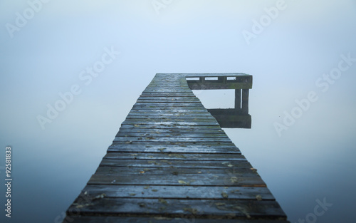 Close up of old, wooden jetty in the autumn fog.