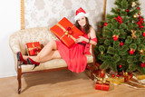 smiling lass wearing red dress and Christmas hat sits on sofa with a big present poster