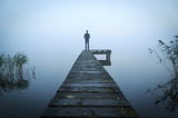Fototapety Man standing on a jetty at a lake during a foggy, gray morning.