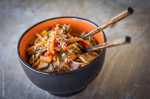Stir fry with vegetables and meat garnished with sesame seeds in bowl with chopsticks Poster