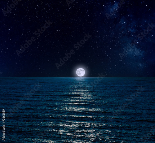 Night sky with full moon, stars and reflection in sea