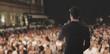 Uomo canta parla sul palco folla