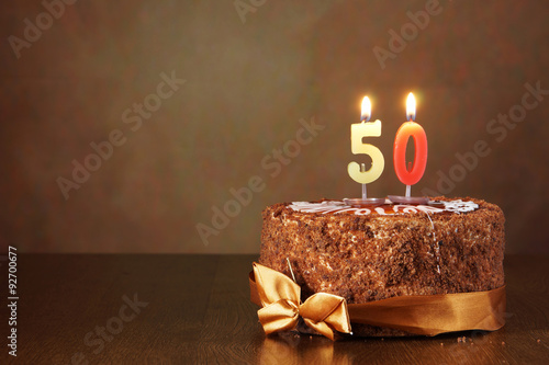 Poster Birthday chocolate cake with burning candles as a number fifty on brown backgrou