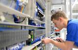 Elektroniker montiert Schaltschrank in der Industrie