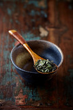 Sencha tea leaves on a wooden spoon