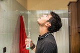 Handsome young man using mouthwash, in bathroom