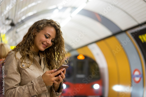 A woman using a mobile phone on the tube underground station, Lo Plakát