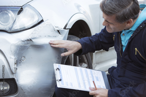 Auto Workshop Mechanic Inspecting Damage To Car And Filling In R