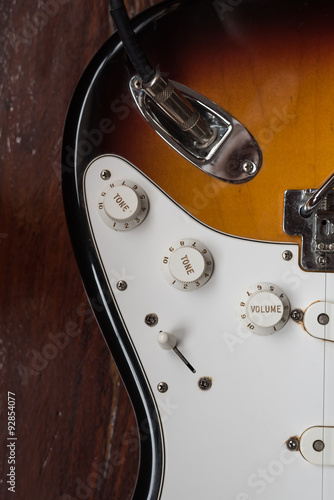 Poster volume and tone adjusting buttons on electric guitar