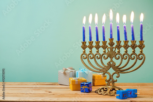 Plakát Jewish holiday Hanukkah background with vintage menorah and gift boxes on wooden