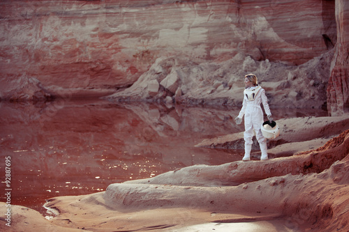 Staande foto Bordeaux Water on Mars, futuristic astronaut without a helmet in another