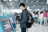 Fototapety Young asian man using self check-in kiosks in airport