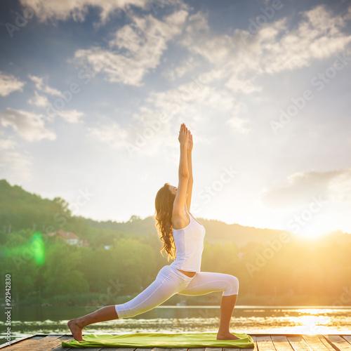 Poster Woman doing yoga on the lake - beautiful lights