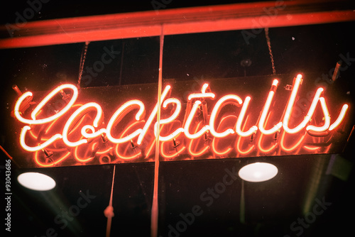 Fototapeta Cocktails Neon Sign Vintage. Cocktails sign in neon hanging in a bar window. Edited with subtle vintage effects.
