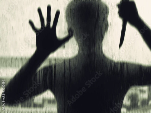 Shadowy figure with a knife behind glass,soft focus Poster