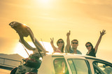 Fototapety Best friends cheering by car road trip at sunset - Group of happy people outdoor on vacation tour - Friendship concept at travel with positive nostalgic emotions - Soft focus due to backlight contrast