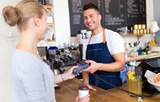 Barista serving customer in coffee shop