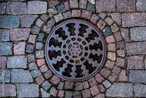 In de dag Tunnel Manhole on old style brick road