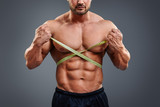 Personal fitness trainer holding tape measure isolated over gray background. Closeup of muscular man measuring his waist. Doing perfect six pack abs.