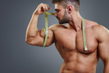 Closeup handsome strong athlete measuring muscle biceps with tape measure isolated over gray background. Bodybuilder tries to measure bicep by himself.