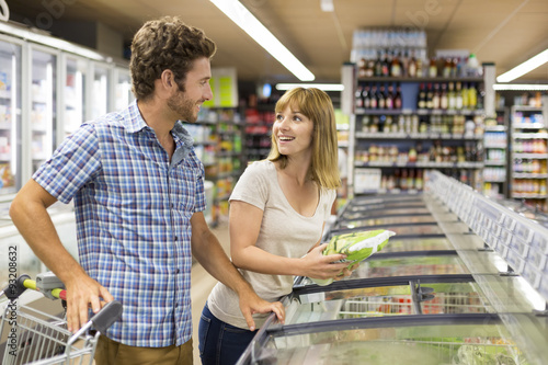 Young couple chooses frozen products in supermarket