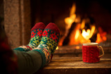 Fototapety Feet in woollen socks by the Christmas fireplace. Woman relaxes by warm fire with a cup of hot drink and warming up her feet in woollen socks. Close up on feet. Winter and Christmas holidays concept.