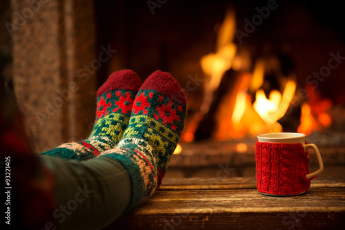 Feet in woollen socks by the Christmas fireplace. Woman relaxes by warm fire with a cup of hot drink and warming up her feet in woollen socks. Close up on feet. Winter and Christmas holidays concept. - 93221405