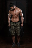 Bodybuilder Exercising Trapezius With Weights poster