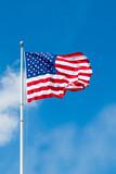 American flag waving against blue sky. Copy space. - 93285023