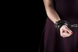 submissive woman wearing a purple dress in leather handcuffs on