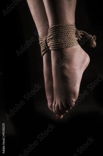 detail suspended bound feet submissive young girl on a black bac
