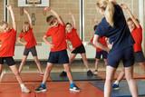 Fototapety Teacher Taking Exercise Class In School Gym