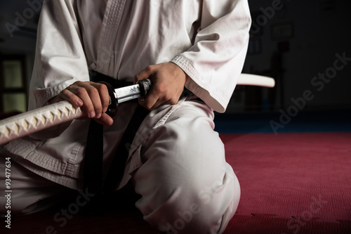 Close up of young martial arts fighter with katana siting in seiza position Poster