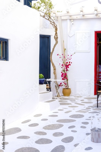 A very traditional alley view of the architecture in Chora,on the greek island Mykonos,Greece.A blue door, windows, a red bougainvillea and flowers outside a whitewashed house and cobble paved street