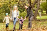 Young family running in leaves