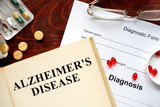 Alzheimers disease  written on book with tablets. Medicine concept.