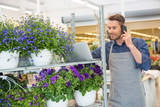 Florist Using Mobile Phone And Laptop In Shop